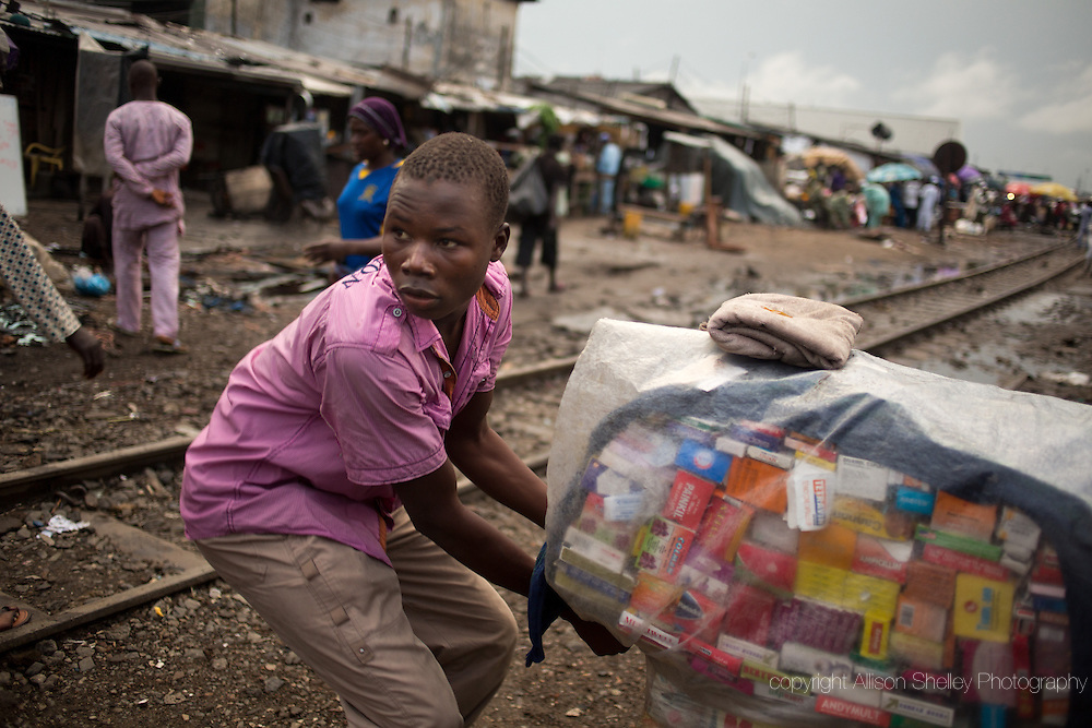 "A local ""hawker"" sells drugs from a basket that he carries on his head, in the Badia neighborhood of Lagos, Nigeria, September 20, 2013. Wares include condoms, made-in-Nigeria herbal remedies and all manner of pills, sometimes including prescription-only drugs used for abortion. Public clinics are supposed to offer free condoms but are often out of stock."
