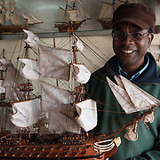 Mauritius. Harel Celestin holds one of the model boats he makes.