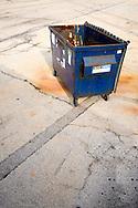 Garbage dumpster in parking lot, empty.
