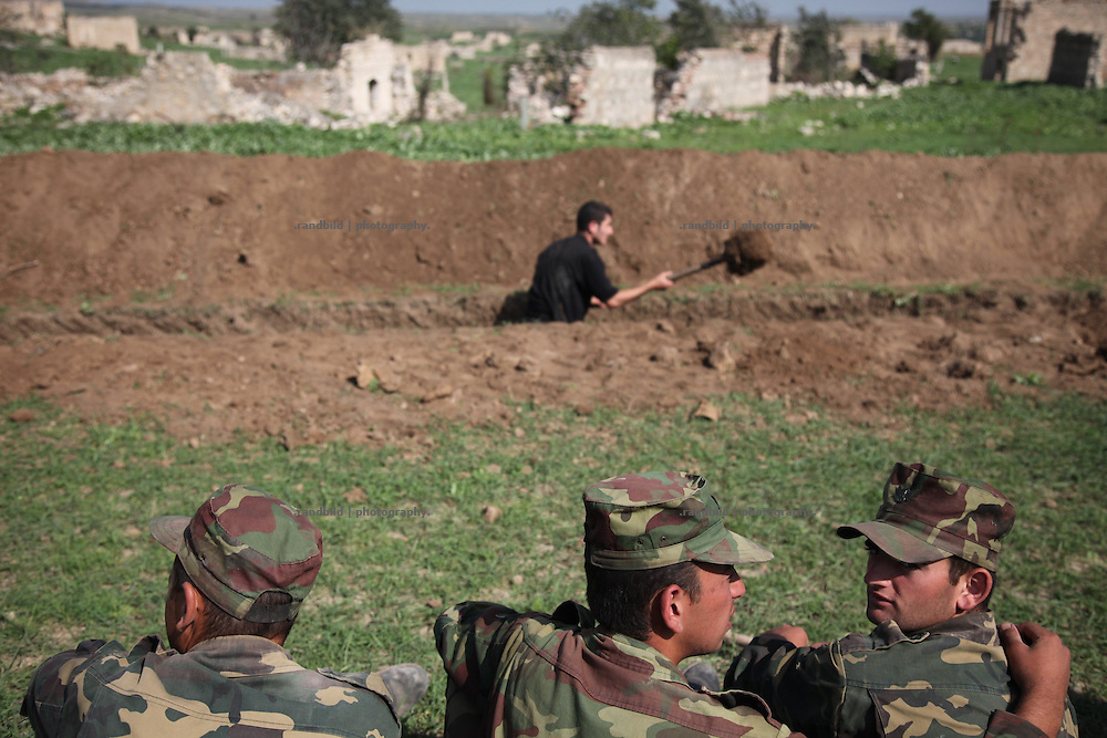 An armenian volunteer supports the army and bury a new trench near the frontline of Nagorno Karabkh to Aserbaijan observed by soldiers.