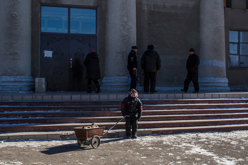 MYRONIVSKYI, UKRAINE - FEBRUARY 17: A boy crouches reflexively at the sound of artillery passing overhead outside a humanitarian aid distribution point at the local House of Culture on February 17, 2015 in Myronivskyi, Ukraine. A ceasefire agreed to by Ukraine and pro-Russian rebel forces has failed to prevent fighting in the nearby town of Debaltseve, where thousands of Ukrainian troops remain and whom rebels claim to have surrounded. (Photo by Brendan Hoffman/Getty Images) *** Local Caption ***