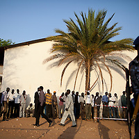 Police watch over residents of Juba waiting to vote on the first day of voting for Southern Sudan's referendum for separation on Jan. 9. 2011 in Juba.