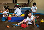In Fukushima City's University kindergarten, children have to play indoors because of fear of radiation so they have created an indoors playground with non contaminated sand where children can play safely.