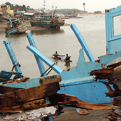Exhausted fishermen who lost their homes, boats and livelihoods try to catch fish form nets in front of a decimated boat after the tsunamis ravaged the coast of India, Africa and Asia January  23, 2005 in Nagapattinum, Tamil Nadu, India.