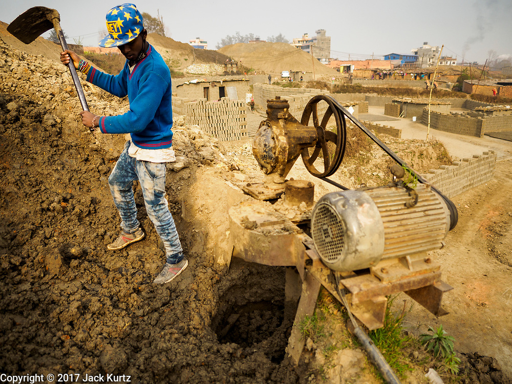 09 MARCH 2017 - BAGMATI, NEPAL:  A workers shovels the clay that will go into bricks at a brick factory in Bagmati, near Bhaktapur. There are almost 50 brick factories in the valley near Bagmati. The brick makers are very busy making bricks for the reconstruction of Kathmandu, Bhaktapur and other cities in the Kathmandu valley that were badly damaged by the 2015 Nepal Earthquake. The brick factories have been in the Bagmati area for centuries because the local clay is a popular raw material for the bricks. Most of the workers in the brick factories are migrant workers from southern Nepal.           PHOTO BY JACK KURTZ