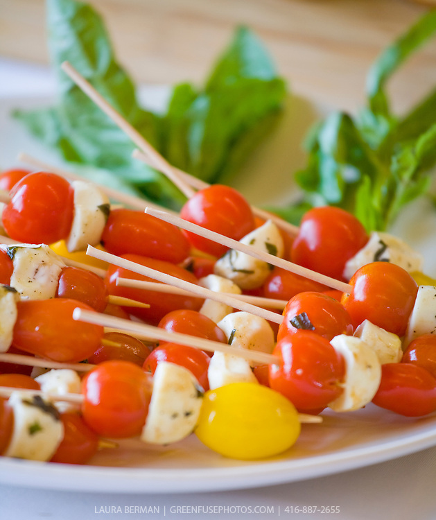 Hors d'oeuvres of red and yellow cherry tomatoes with herbed bocconcini cheese, with basil leaves.
