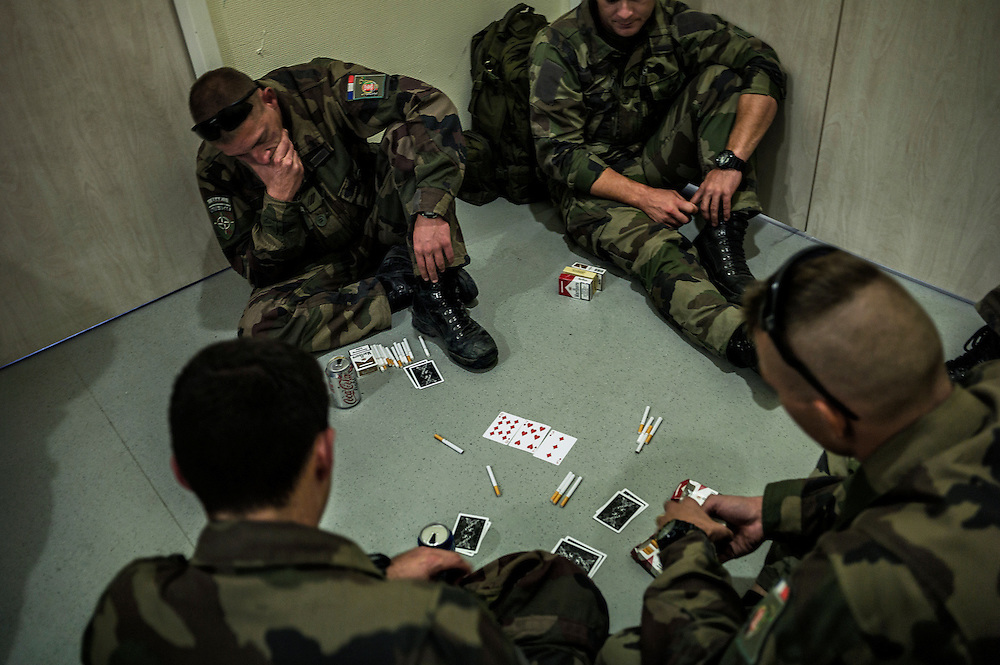 16th BC French unit soldiers play poker as they wait for their plane to go back to France, on September 29, 2012 in KAIA airport in Kabul. AFP PHOTO / JEFF PACHOUD