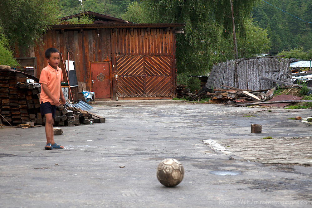 Asia, Bhutan, Bumthang. Kid plays with soccer ball in Bhutan.