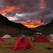 Orange sunset light on clouds over red tents in Alpamayo Valley at 13,860 feet / 4200 meters in the Cordillera Blanca, Andes Mountains, Peru, South America. Day 7 of 10 days trekking around Alpamayo in Huascaran National Park (UNESCO World Heritage Site).
