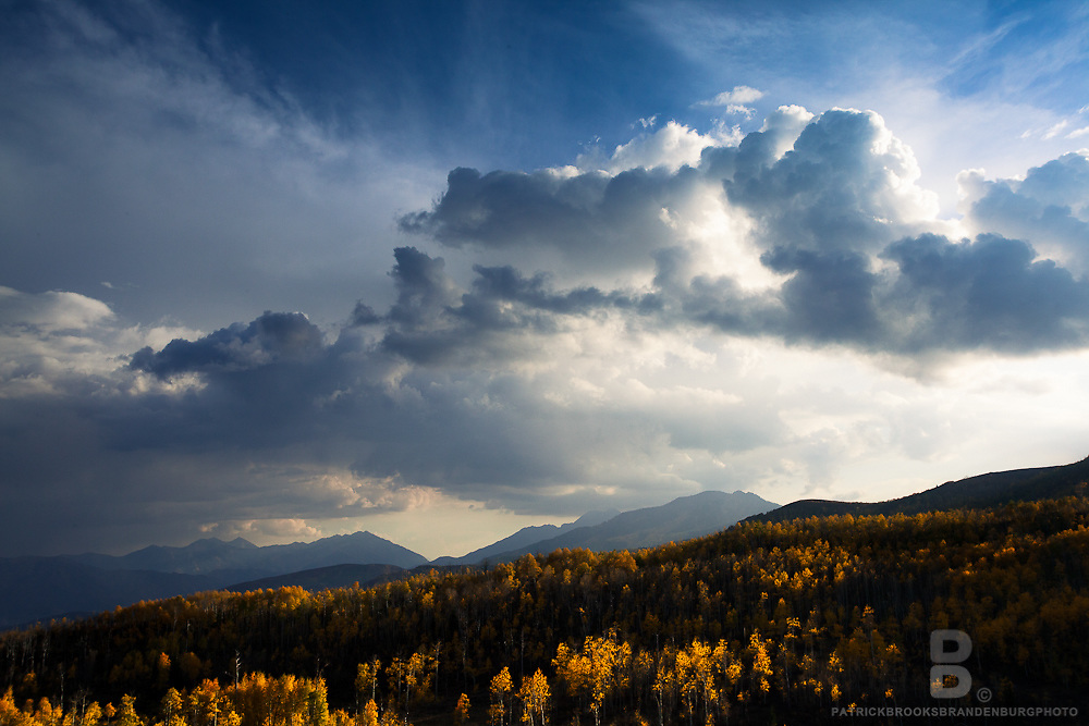 A dramatic sky and light shine on the golden aspens along the Guardsman Pass in the Wasatch Range in Utah.