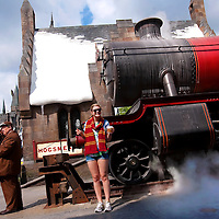 ORLANDO, FL -- May 29, 2010 -- Anna Buck of Minneapolis, Minn., beams with a wand, a mug of Butterbeer, and a scarf as she checks out The Hogwarts Express as Mogsmead Station at The Wizarding World of Harry Potter at Universal Orlando in Orlando, Fla., on Saturday, May 29, 2010.  The 20-acre park features a new ride inside the Hogwarts Castle, shops along the village of Hogsmeade, and is scheduled to officially open on June 18.