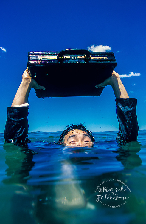 Australia, Queensland, businessman in sea struggling to keep briefcase out of water.  MR available.