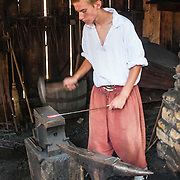 """A costumed historical interpreter pounds hot iron into a nail in the blacksmith building at Jamestown Settlement, which recreates the 1610-14 James Fort in Virginia, USA. Jamestown Settlement, operated by the state's Jamestown-Yorktown Foundation, chronicles 1600s Virginia and the convergence of Powhatan Indian, European, and west central African cultures. Jamestown, the first permanent English settlement in the Americas, was founded as James Fort in 1607 within an area controlled by the Paspahegh tribe, which was part of the Powhatan Confederacy of tribes, Tsenacommacah, comprised of about 14,000 native people ruled by Wahunsonacock (sometimes called Powhatan). Created as part of the 350th anniversary celebration in 1957 as """"Jamestown Festival Park,"""" Jamestown Settlement is adjacent to the complementary """"Historic Jamestowne"""" museum (which is on Jamestown Island, is the actual historic and archaeological site where the first settlers lived, and is run by the National Park Service and Preservation Virginia). For licensing options, please inquire."""