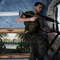 SYRIA, ALEPPO : A Syrian rebel from the Free Syrian Army (FSA) is about to pass through a hole in the side of an apartment in the northern restive city of Aleppo on September 25, 2012. The FSA have created a series of hidden routes to combat regime positions, where they continue to fight following a major offensive by the government army. ALESSIO ROMENZI