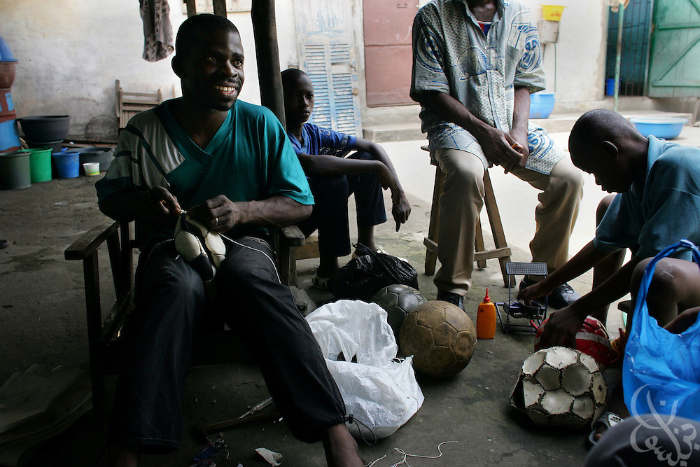 """Blaise N'cho, age 29, spends his Sunday afternoon repairing footballs in the Abobo neighborhood of Abidjan, Côte d'Ivoire.  N'Cho, a shoe repairman, who's skill at repairing balls has earned him the reverent nickname  """"Le Seigneur"""", or """"the Lord"""", charges $1 per ball for most repairs and works out of his small family home."""
