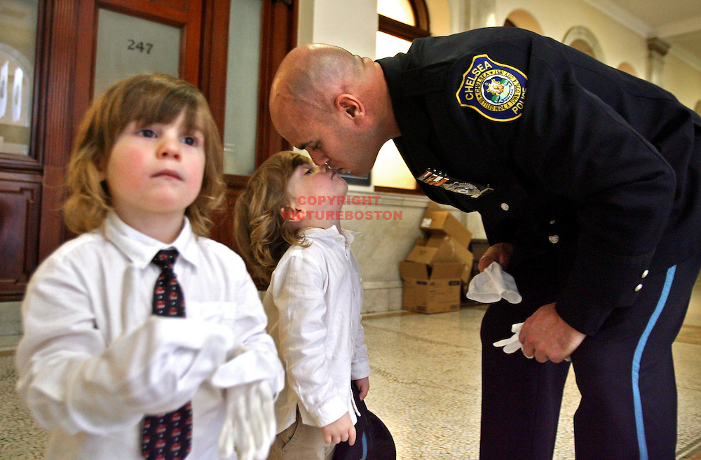 (10/26/07-Boston,MA) Annual Massachusetts State Police Awards Ceremony at the State House. Here, Chelsea Police Detective Scott Conley kisses 3 year old twin sons LtoR Aidan and Max after the veteran officer received the Superintendent's Commendation for his exceptional contribution in assisting the Massachusetts State Police and the North Shore Gang Task Force. Staff photo by Mark Garfinkel