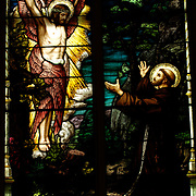 A stained glass window at St. Francis Xavier Church depicts Jesus appearing to Francis of Assisi.
