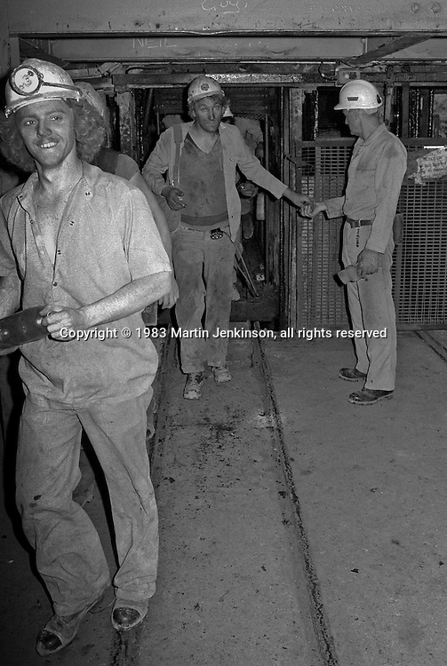 Banksman, Alan Gilburn,collecting checks from Stefan Gryzelka as miners come up from underground at Markham Main Armthorpe Colliery. National Coal Board, Doncaster Area 21/06/1983.