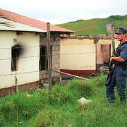 A South African Police officer near some burned out buildings atthe hamlet of Shoboshobane, on the KwaZulu/Natal South Coast.  On Christmas Day, the ANC village was attacked by Inkatha neighbours killing more than 20 residents, and driving the rest into refugee camps.  December 26th, 1995.