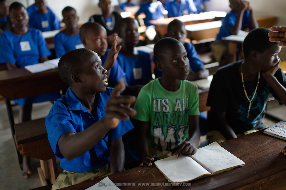 A boy raises his hand to answer a question during a presentation on Menstrual Hygiene Management at Agwait Primary School near Tororo in Eastern Uganda on 1 August 2014.