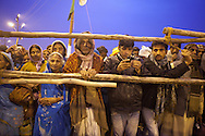 Devotees watching the procession of Sadhus, the Basant Panchami Snan. 15th of February, Allahabad 2013. // The Maha Kumbh Mela is believed to be the single largest religious gathering in the world. It's a sacred pilgrimage celebrated every twelve years. In 2013 it has taken place in Allahabad, in the confluence of the rivers Ganga, Yamuna and Saraswati. Millions of hindu people gather on a single day for a ritual bath in the sacred waters of Ganga. The event congregate millions of devotees, sadhus and sadhvis of all the akharas coming from all over India.