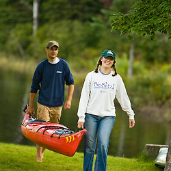 A couple carries their kayak ashore at Lake Francis State Park in Pittsburg, New Hampshire.
