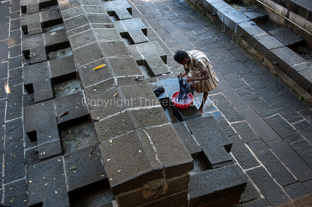 Mahébourg. Woman washing clothes at a now nearly unused dhobi ghat. A public space for washing clothes.