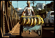 Man rolls produce cart laden with bananas and oranges across bridge in Rio Branco, Acre. Brazil