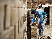 03 MARCH 2017 - BAGMATI, NEPAL: A workers stacks uncooked bricks at a brick factory in Bagmati, near Bhaktapur. There are almost 50 brick factories in the valley near Bagmati. The brick makers are very busy making bricks for the reconstruction of Kathmandu, Bhaktapur and other cities in the Kathmandu valley that were badly damaged by the 2015 Nepal Earthquake. The brick factories have been in the Bagmati area for centuries because the local clay is a popular raw material for the bricks. Most of the workers in the brick factories are migrant workers from southern Nepal.       PHOTO BY JACK KURTZ