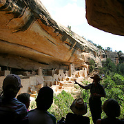 "Park Ranger Amanda Kuhnel (right standing and pointing), 23, points out some of the features of the Cliff Palace dwelling during an hour-long tour at Mesa Verde National Park near Cortez, Co. on Wednesday June 28, 2006. It is Kuhnel's first year working at the park and said the National Park Service had hired additional interpretive guides in the park this summer to handle the increased number of visitors for its 100th birthday. She said, ""my tours have all been sold out"". On June 29, 1906 Theodore Roosevelt designated Mesa Verde a national park, the first cultural national park in the history of the world. The park will celebrate it's 100th birthday with a weekend of events, dancing, musical entertainment and special tours of some of the cliff dwellings. Cilff Palace is the largest of all the dwellings at Mesa Verde with 150 rooms and 21 kivas..(MARC PISCOTTY/ © 2006)"
