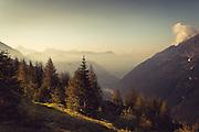 Rising sun and morning fog in Chiareggio, Valmalenco, Italy - sen from a nearby mountain side