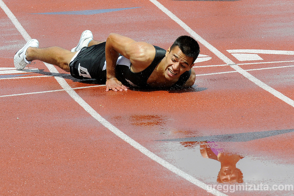 Payette senior Chris Beltran lies on the finish line in lane 3 while the face of Snake River's Logan Bingham, who is coming up in lane 2, is reflected in a puddle on the track during heat #2 of the Idaho Track & Field Championships 3A 300m hurdles on May 23, 2008 at Boise State University's Bronco Stadium.
