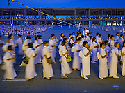 "22 FEBRUARY 2016 - KHLONG LUANG, PATHUM THANI, THAILAND: People participate in the procession around the chedi during the Makha Bucha Day service at Wat Phra Dhammakaya.  Makha Bucha Day is a public holiday in Cambodia, Laos, Myanmar and Thailand. Many people go to the temple to perform merit-making activities on Makha Bucha Day, which marks four important events in Buddhism: 1,250 disciples came to see the Buddha without being summoned, all of them were Arhantas, Enlightened Ones, and all were ordained by the Buddha himself. The Buddha gave those Arhantas the principles of Buddhism, called ""The ovadhapatimokha"". Those principles are:  1) To cease from all evil, 2) To do what is good, 3) To cleanse one's mind. The Buddha delivered an important sermon on that day which laid down the principles of the Buddhist teachings. In Thailand, this teaching has been dubbed the ""Heart of Buddhism."" Wat Phra Dhammakaya is the center of the Dhammakaya Movement, a Buddhist sect founded in the 1970s and led by Phra Dhammachayo.      PHOTO BY JACK KURTZ"