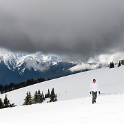 A man and his dog on Hurricane Ridge, with the lodge in background. The weather can change quickly up there... a sunny day was interrupted by this low cloud bank moving through, and a few hours later it was in total whiteout there. The Bailey Range is in the distance.