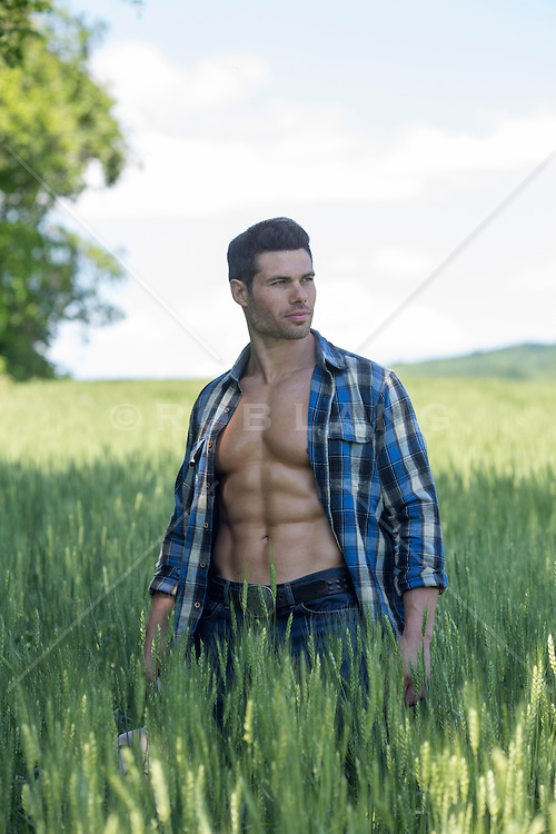 man with great abs standing in a field with an open shirt