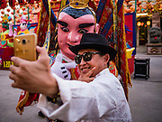 28 JANUARY 2017 - SAMUT PRAKAN, SAMUT PRAKAN, THAILAND: A Chinese tourist takes a selfie with a Chinese entertainer at the Chinese New Year Lantern Festival at the Tham Katanyu Foundation shrine in Samut Prakan, a suburb about 15 miles from Bangkok. More than 5,000 handmade lanterns imported from Taiwan are hung on the grounds of the shrine. Some of the lanterns are traditional Chinese lanterns, others are in the shapes of people or deities. There is also traditional Chinese entertainment, likes lion dances, at the festival.     PHOTO BY JACK KURTZ