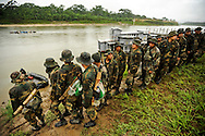 Counternarcotics forces line up to cross a river during a patrol to eradicate coca patches that are over the legal limit in Chapare. It's estimated that 90 percent of coca from the Chapare goes to the drug trade.