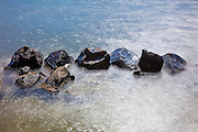 A long exposure captures the spray of Lake Washington waves crashing over a line of large rocks along the beach of Saint Edward State Park, Kenmore, Washington.