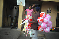 A vendor tries to sell a woman balloons along the beach in Colombo, Sri Lanka, July 3, 2009. With the end of the 26 war between the Sri Lankan government and the LTTE, security in the capital city remains on high alert.