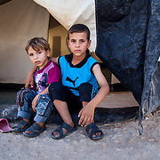 Brothers Amir, 5, and Ibrahim, 7, sit in front of their tent in Zaatari camp for Syrian refugees in Jordan. August, 2013.