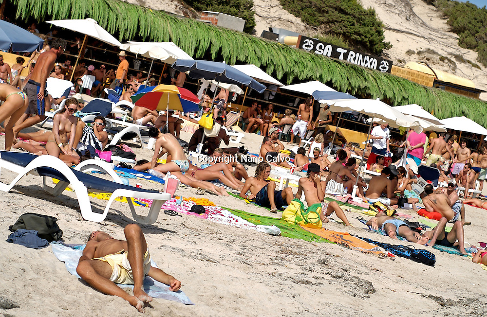 People enjoying sun and beach next to popular Sa Trinxa, in Salinas, Ibiza