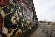 An abandoned building in Urban Atlanta with Urban Grafitti Artwork painted on it's outside wall and an empty spray can laying on the ground in front of it..