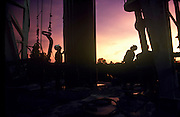 Silhouette of oil rig workers looking up against a pink sky at dusk, Webster, Texas