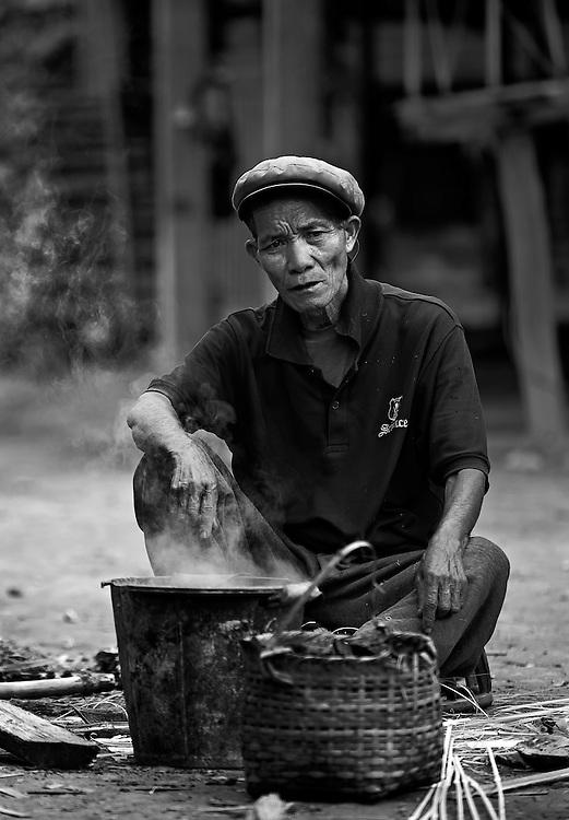 A man cooking in his village near the Nam Tha (river), Laos.