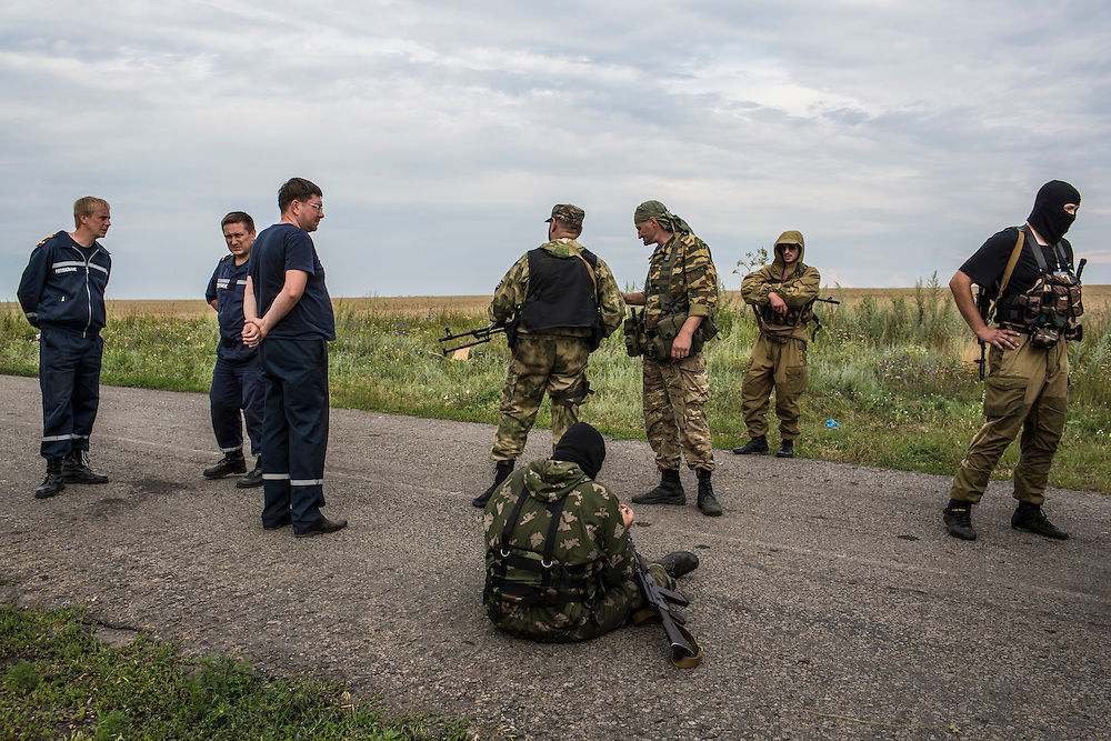 GRABOVO, UKRAINE - JULY 19: Pro-Russia separatist fighters and emergency personnel gather near the scene of the crash of Malaysia Airlines flight MH 17 on July 19, 2014 in Grabovo, Ukraine. Malaysia Airlines flight MH17 was travelling from Amsterdam to Kuala Lumpur when it crashed killing all 298 on board including 80 children. The aircraft was allegedly shot down by a missile and investigations continue over the perpetrators of the attack. (Photo by Brendan Hoffman/Getty Images) *** Local Caption ***