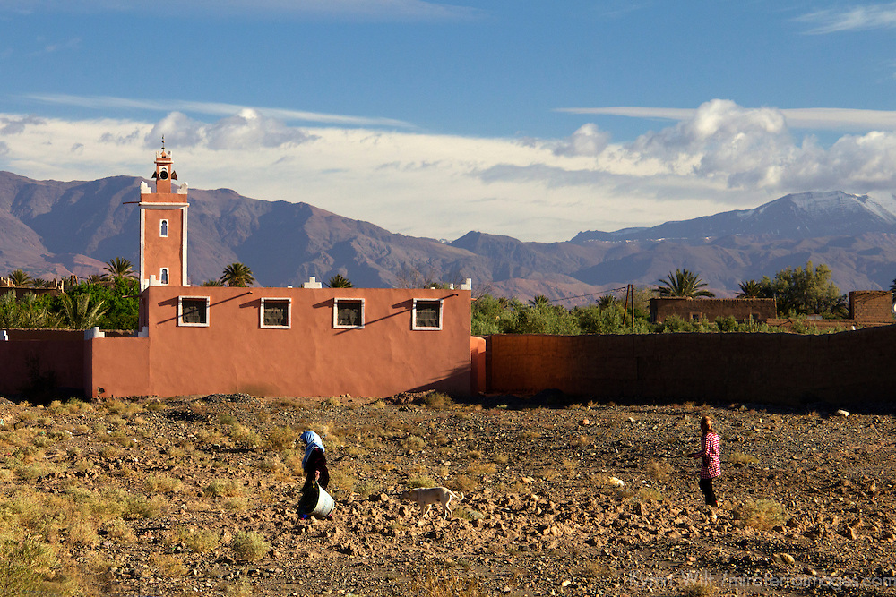 Africa, Morocco, Skoura. Women passing Mosque in Skoura.