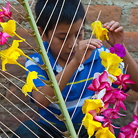 PANCHIMALCO , EL SALVADOR - MAY 08 : A Salvadoran boy decorates palm fronds with flowers during the Flower & Palm Festival in Panchimalco, El Salvador on May 08 2016
