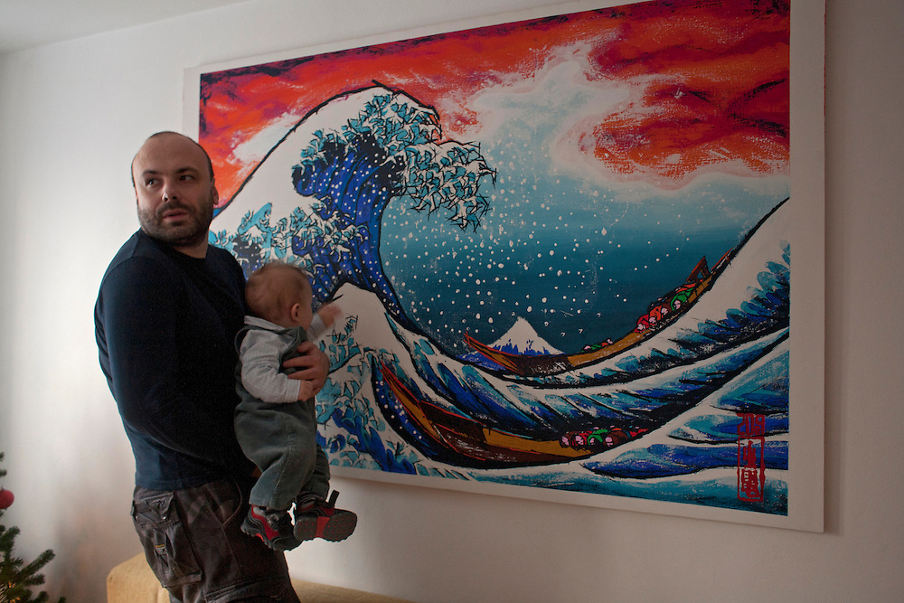 Muha Kafedzic and his son Isak get close to one of his recent paintings in their Sarajevo home. The series is inspired by late century Japanese art but he adopts modern technique and the limitations of life in Sarajevo. Kafedzic encourages his son to touch and manipulate the print, getting to know the art personally. ..