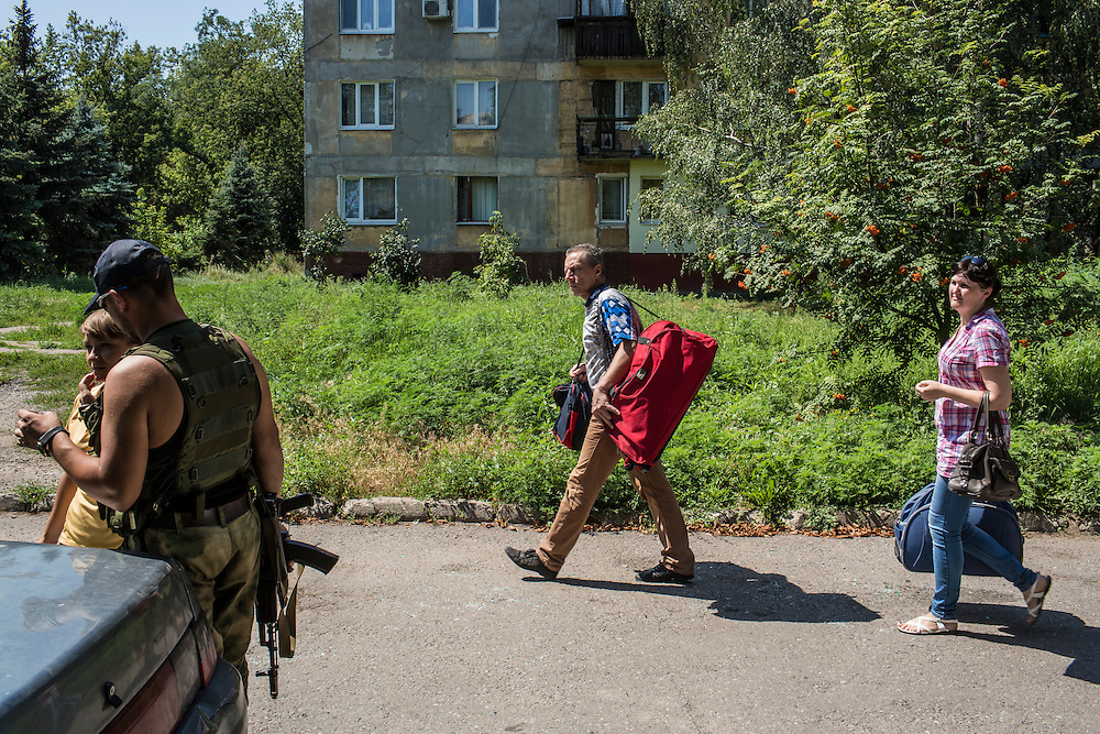 Residents of the Ploshchadka neighborhood, which has been heavily bombarded in recent days, take their belongings past pro-Russia rebels on Wednesday, July 30, 2014 in Donetsk, Ukraine.