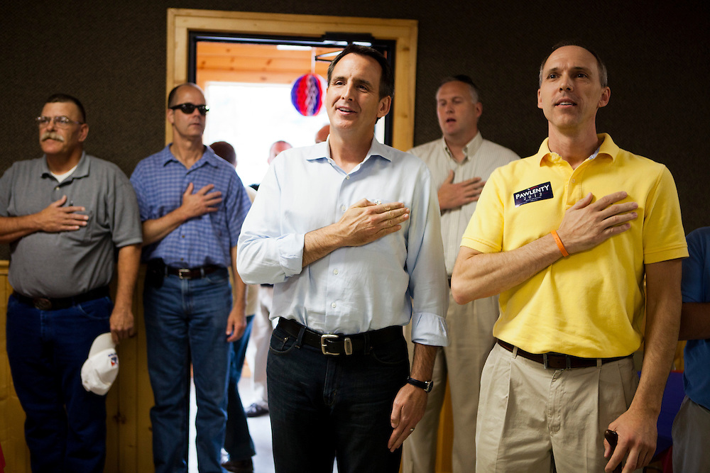 Republican presidential hopeful Tim Pawlenty, center, says the pledge of allegiance at the beginning of a campaign stop on Tuesday, August 9, 2011 in Humboldt, IA.